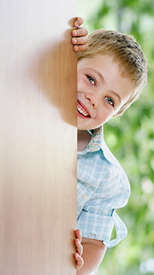 Photo of smiling boy peeking around corner